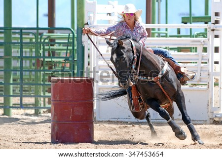 Beautiful cowgirl riding a horse around a barrel during a rodeo. - stock photo