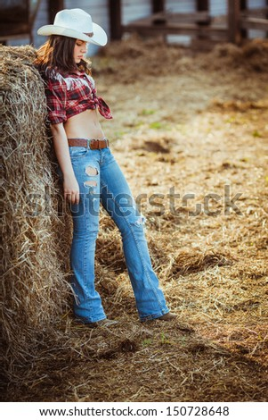 beautiful cowgirl style model posing near hay - stock photo