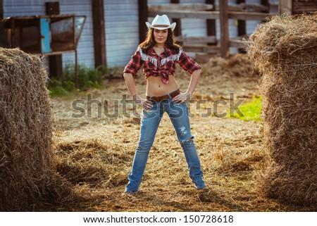 beautiful cowgirl style model posing on farmland - stock photo
