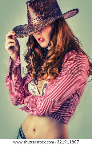 Beautiful cowgirl style woman wearing cowboy hat, studio shot