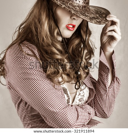 Beautiful cowgirl style woman wearing cowboy hat, studio shot - stock photo
