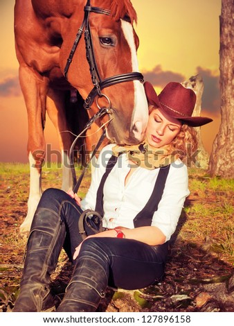 Beautiful  cowgirl with her red horse - stock photo