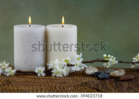 Beautiful crab apple tree blossoms with stones candle on mat - stock photo