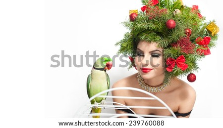 Beautiful creative Xmas makeup and hair style indoor shoot. Beauty Fashion Model Girl. Winter. Beautiful girl with green parrot in studio. Attractive girl with Christmas tree accessories - stock photo