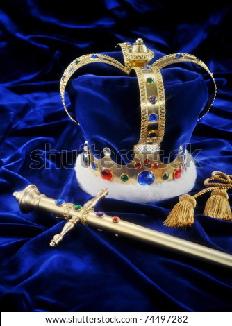 Beautiful crown and sword on royal blue fabric with soft window light and copy space - stock photo