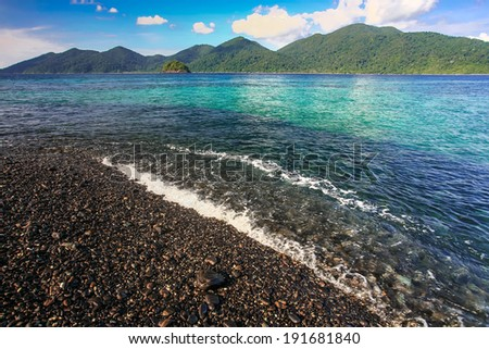 Beautiful crystal clear sea with black pebble beach at tropical island, Koh Lipe, Andaman sea, Thailand - stock photo