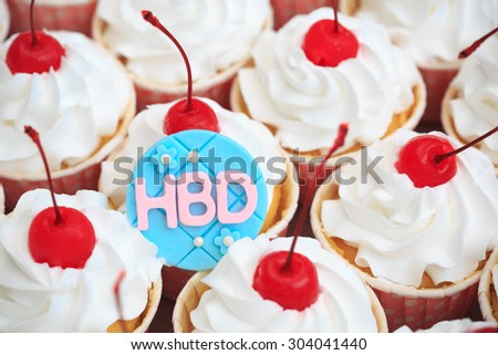 Beautiful cup cake with red cherry on top and happy birthday words