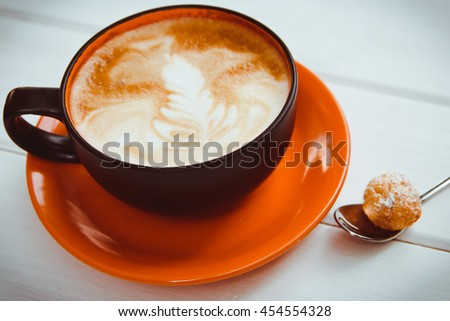 Beautiful cup of cappuccino with foam and coffee spoon stands on the table