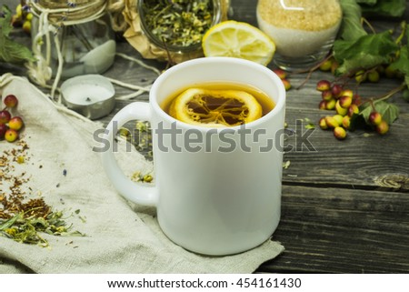 beautiful Cup of tea on wooden background with lemon and herbs
