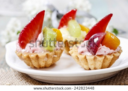 Beautiful cupcakes decorated with fresh fruits: strawberry, peach, kiwi - stock photo