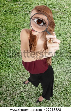 Beautiful curious woman looking through a magnifying glass - stock photo