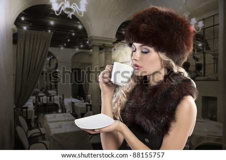 beautiful curly blonde elegant woman drinking a hot cup of tea and wearing a fur stole and a huge fur cap - stock photo