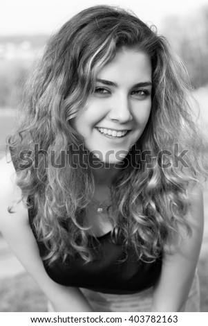 Beautiful curly brunette. Close-up portrait in bw