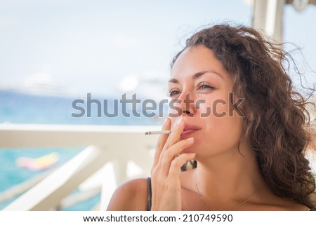 Beautiful curly brunette with a cigarette and champagne. Girl in a cafe on the beach, smoking, drinking, and enjoying life. Cigarettes, champagne, beauty, sea. The concept of an unhealthy lifestyle. - stock photo