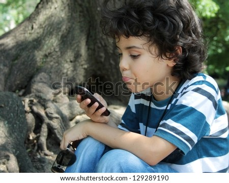Beautiful curly child playing with cellphone sitting in the park - stock photo