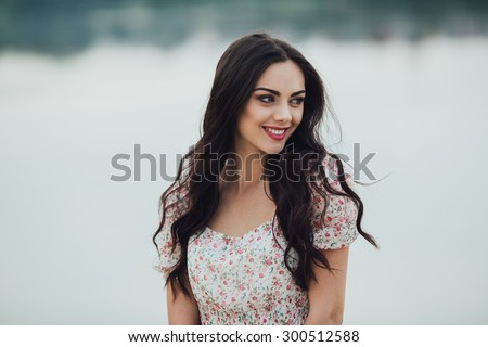 Beautiful, curly girl posing on a background of water and smiling
