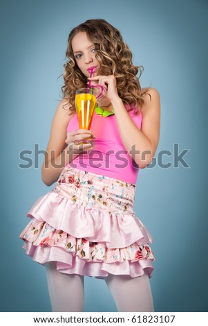 Beautiful curly-haired blond woman with cocktail on the blue background - stock photo