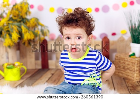 Beautiful curly-haired boy. Easter decorations - stock photo