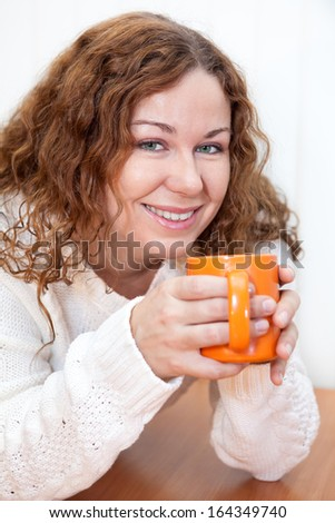 Beautiful curly haired woman in white wool sweater with cup of tea or coffee. White background - stock photo