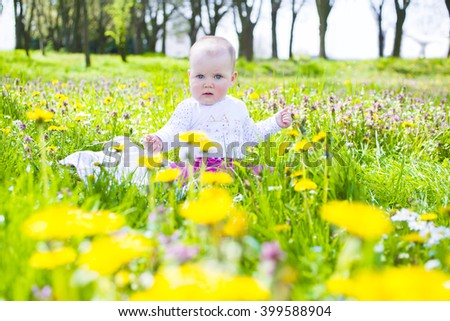 Beautiful curly little girl among spring flowers - stock photo