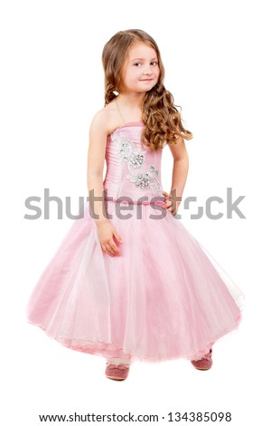 Beautiful curly little girl posing in pink dress. Isolated on white