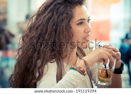beautiful curly long brunette hair moroccan woman with cocktail at the bar - stock photo