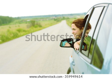 Beautiful curly redhead woman looking at far away.  reflection in a car window and mirror. Asphalt road in perspective. Summer nice day. Cute young girl sit inside car.