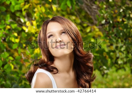 Beautiful curly smiling girl against green foliage - stock photo