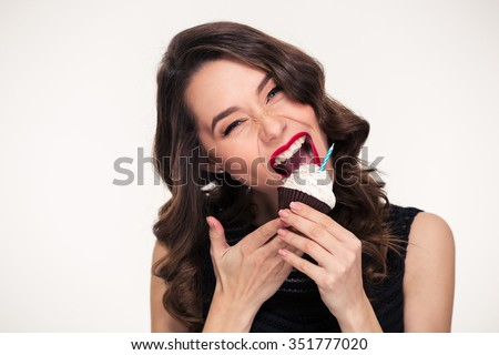 Beautiful curly young woman with bright makeup in retro style biting birthday cupcake with candle over white background - stock photo