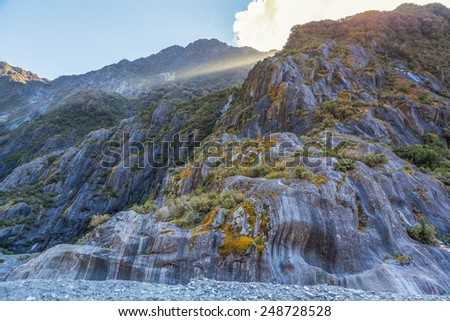 Beautiful curvy rock formations carved by the retreat of Franz Josef Glacier, South Island, New Zealand - stock photo