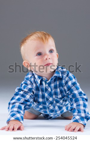 Beautiful cute baby on  grey background - stock photo