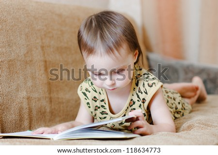 Beautiful cute baby reading a book while lying on the couch.