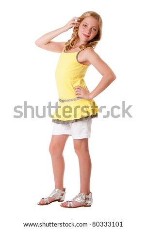 Beautiful cute blond young teenager girl wearing fashion clothes, yellow layered shirt withy white shorts and belt, isolated.