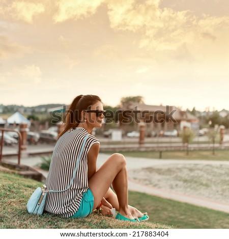 Beautiful cute fashionable girl sitting at sunset - stock photo