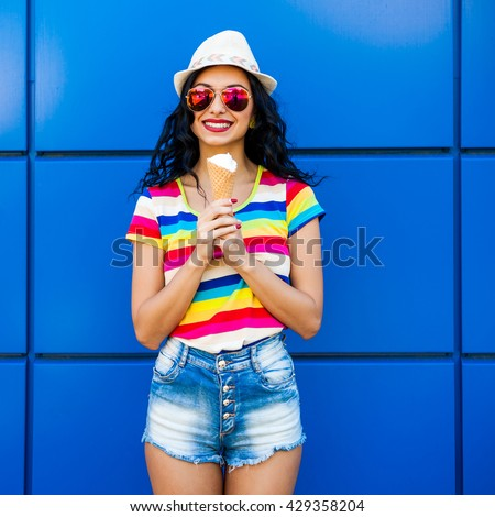 Beautiful cute funny amazing young hipster teen girl eating ice cream cone, laughs happy, bright casual wear, denim shorts, striped, colored T-shirt, rainbow, blue background, urban style, sunglasses - stock photo