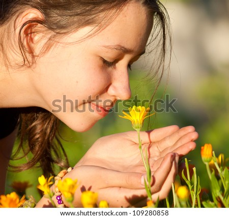 Beautiful cute girl smelling yellow flower in garden - stock photo