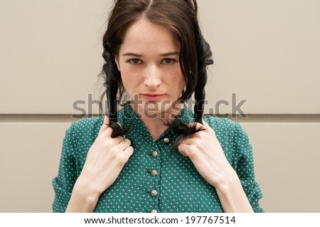 Beautiful cute girl with natural look wearing a green dress with white dots, making pigtails or ponytails with her hair - stock photo