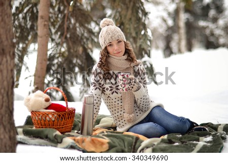 Beautiful,cute,happy,light girl sitting on a blanket in the winter in the cold,snow,fosest,forest and drinking  cup of warm tea,background,little,december,january,february,people,child,portrait,year - stock photo