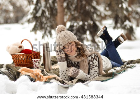 Beautiful,cute,happy,light girl sitting on a blanket in the winter in the cold,snow,fosest,forest and drinking  cup of warm tea,background,little,december,january,february,people,child,portrait,year