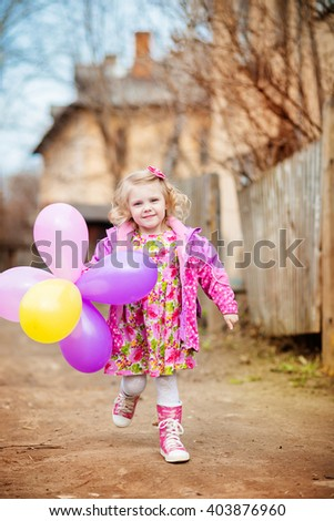 beautiful, cute little blonde girl with blond curly hair in a pink gingham dress jacket and rubber boots, laughing with balloons on walk, early spring / late autumn