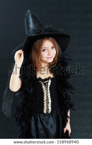 beautiful cute little girl in witch halloween costume over dark background