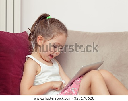 beautiful cute little girl playing with tablet computer at home - stock photo