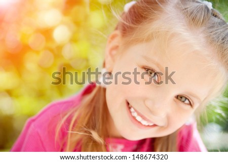 beautiful cute little girl smiling in a park close-up - stock photo