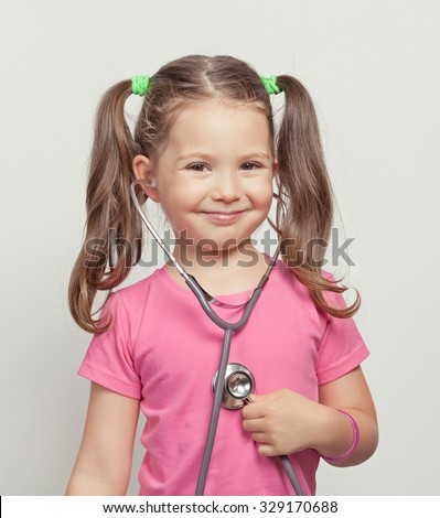 beautiful cute little girl with stethoscope. little girl playing in doctor - stock photo