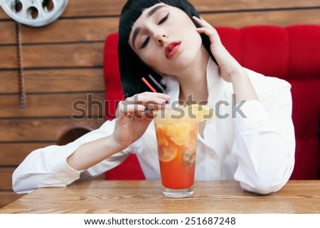 Beautiful cute woman in a black wig and the white shirt. Closeup portrait of a young girl over red background. Perfect bright makeup. Red lips. Pulp Fiction. With cocktail. - stock photo