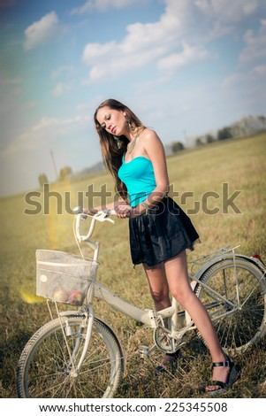 beautiful cycling adventure: sexy young pretty lady having fun with bicycle in fields under bright blue summer sky on green copy space background, portrait