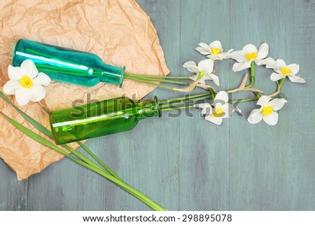 Beautiful daffodils in vases on wooden background - stock photo