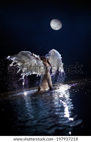 Beautiful dancing white angel on the moon background - stock photo