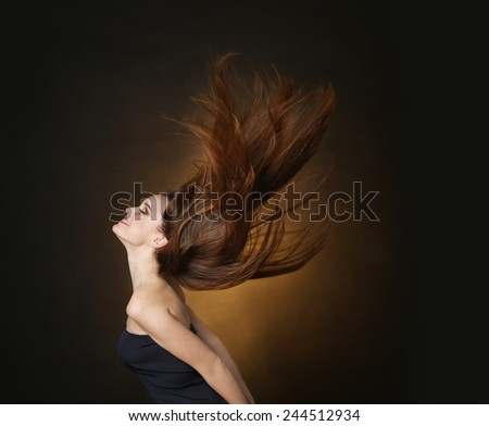 Beautiful dancing young woman with flowing long hair on dark brown background - stock photo