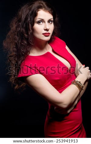 Beautiful, daring brunette woman in a red dress on a black background